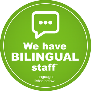 A green circle which features the text 'We have bilingual staff: languages listed below'. A graphic of a speech bubble with an ellipsis inside.