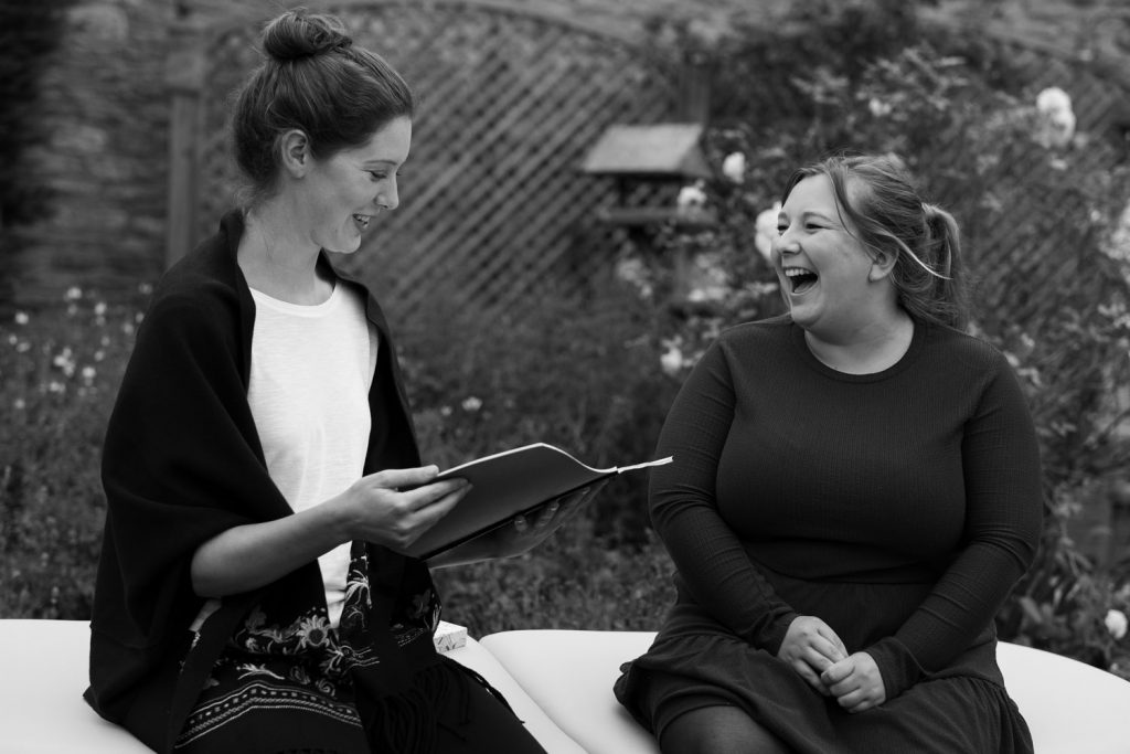 One woman reading from a notebook and the lady aside her is having a big giggle. The image is black and white.