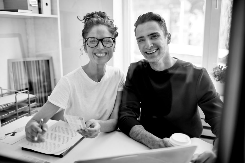 An image of a woman with glasses wearing a white shirt writing in her workbook, sitting alongside a man wearing a black pullover drinking a takeaway coffee.