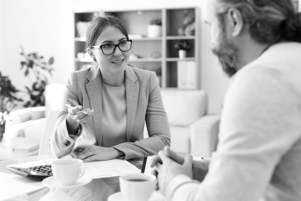 A woman in a blazer is explaining a document to a man in a jumper with a beard. There is a cup of tea on the table which is between the two people.