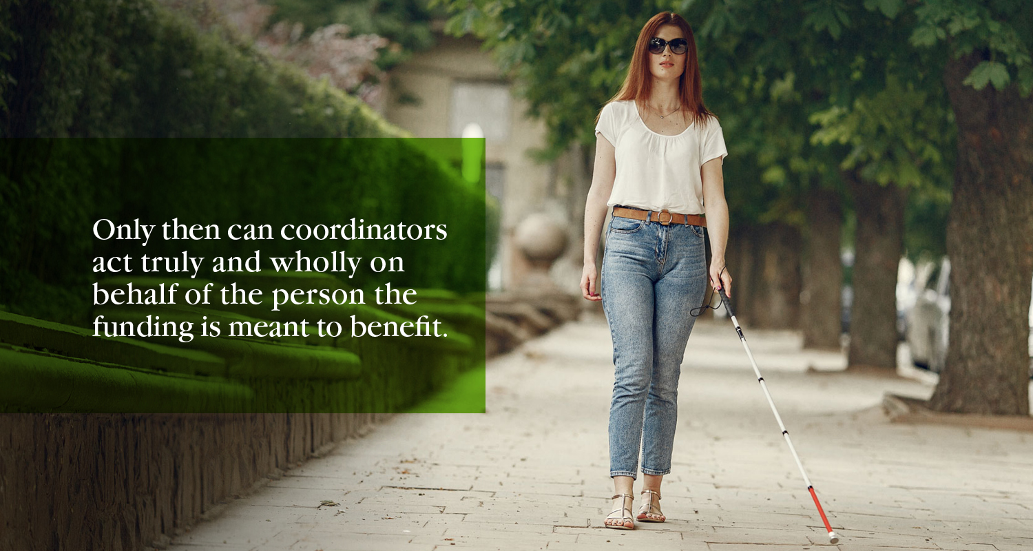 A woman with low vision has red hair and sunglasses. She is wearing a white shirt and acid wash jeans. She is walking alongside a row of trees using a blind cane. The text to the left of the image reads: Only then can coordinators act truly and wholly on behalf of the person the funding is meant to benefit.